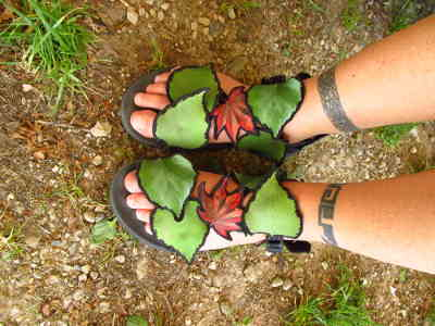 Two feet in sandals, decorated with green leaves